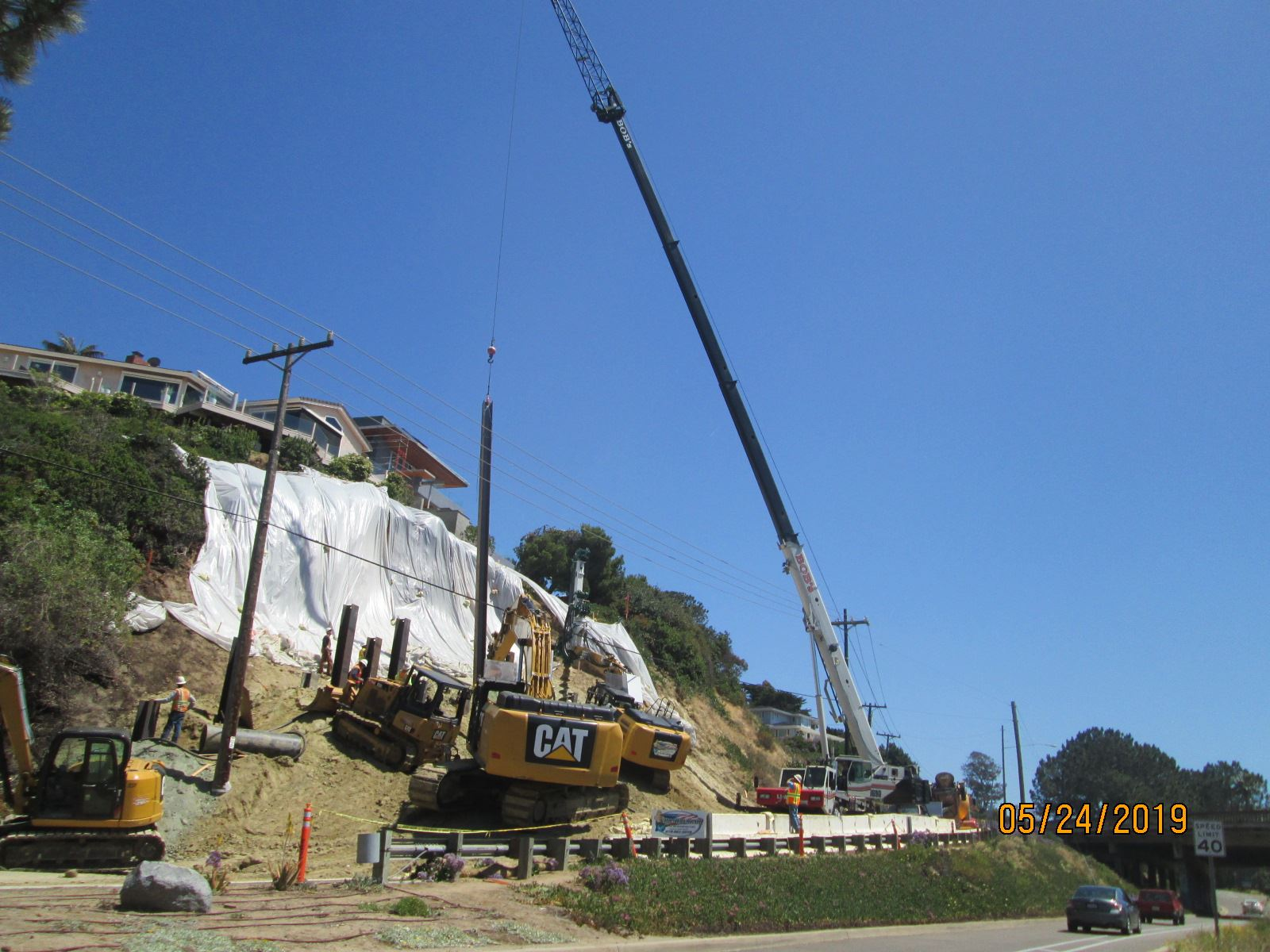 Crane lowers beam at Jimmy Durante Boulevard bluff slide
