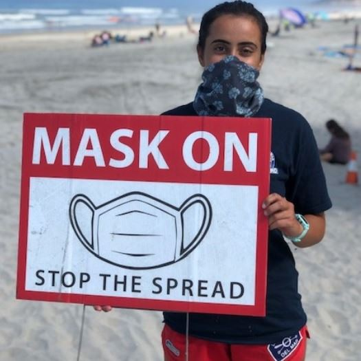Lifeguard holds Mask On sign